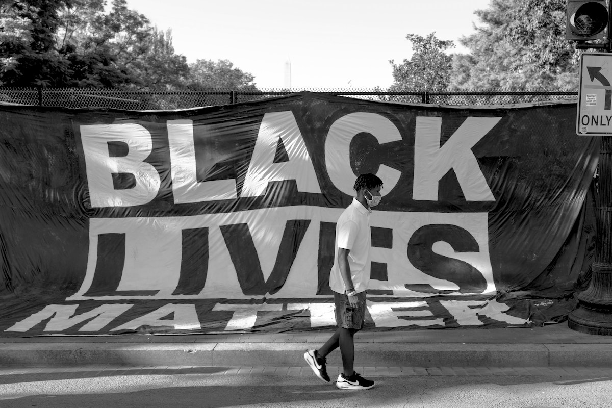 young man walking by black lives matter sign